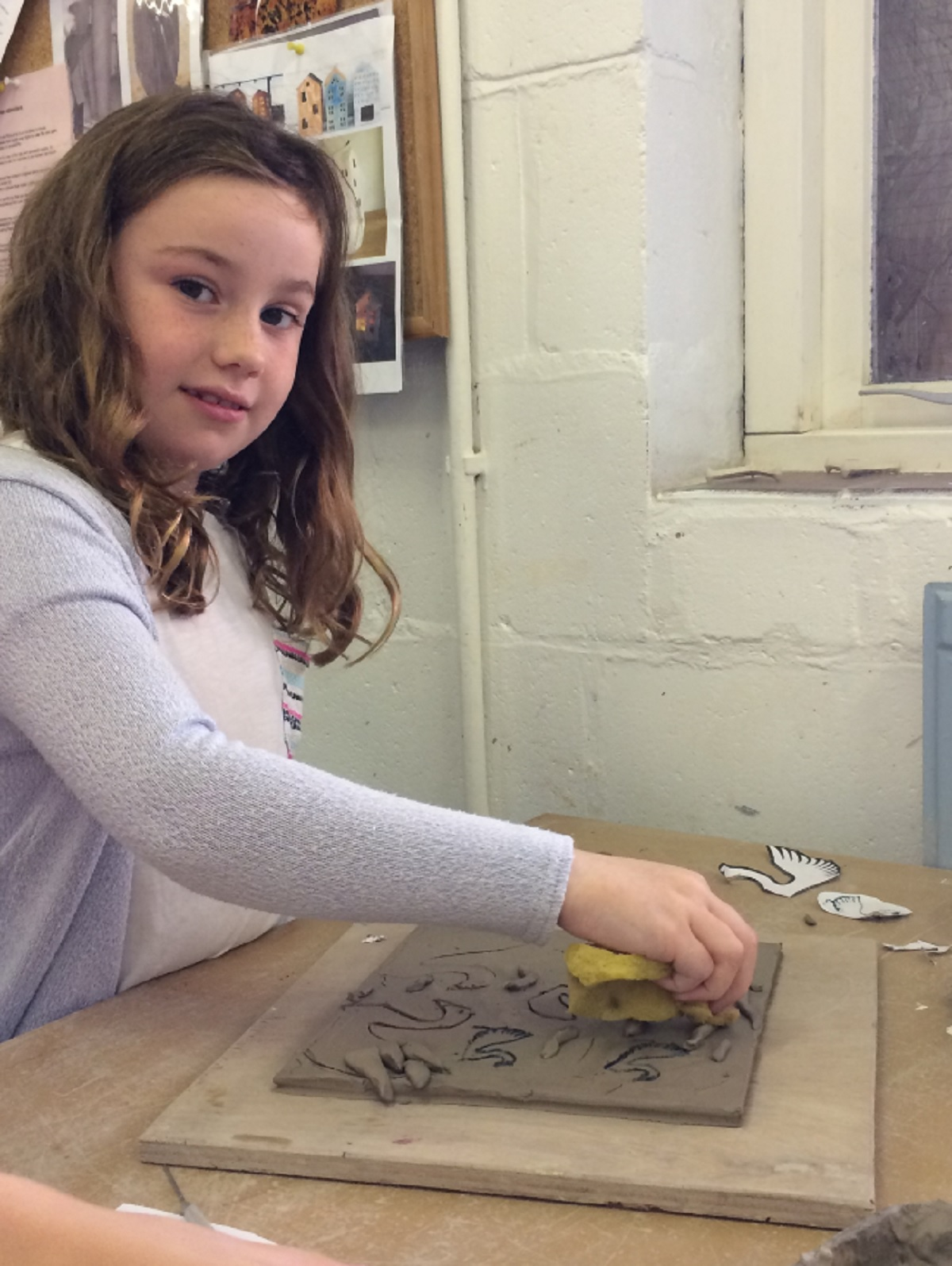 COMPETITION: Heidi, aged eight, working on her ceramic plate for the art competition.