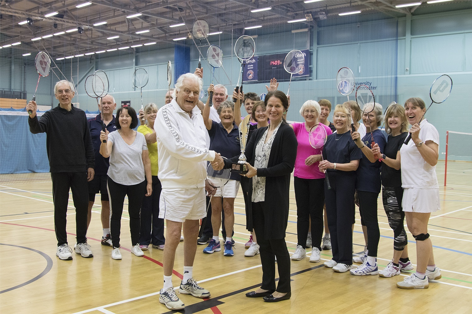 Godfrey Harvey (front left) receiving his award from Dr Susie Hart. Pictured with the seniors badminton programme.