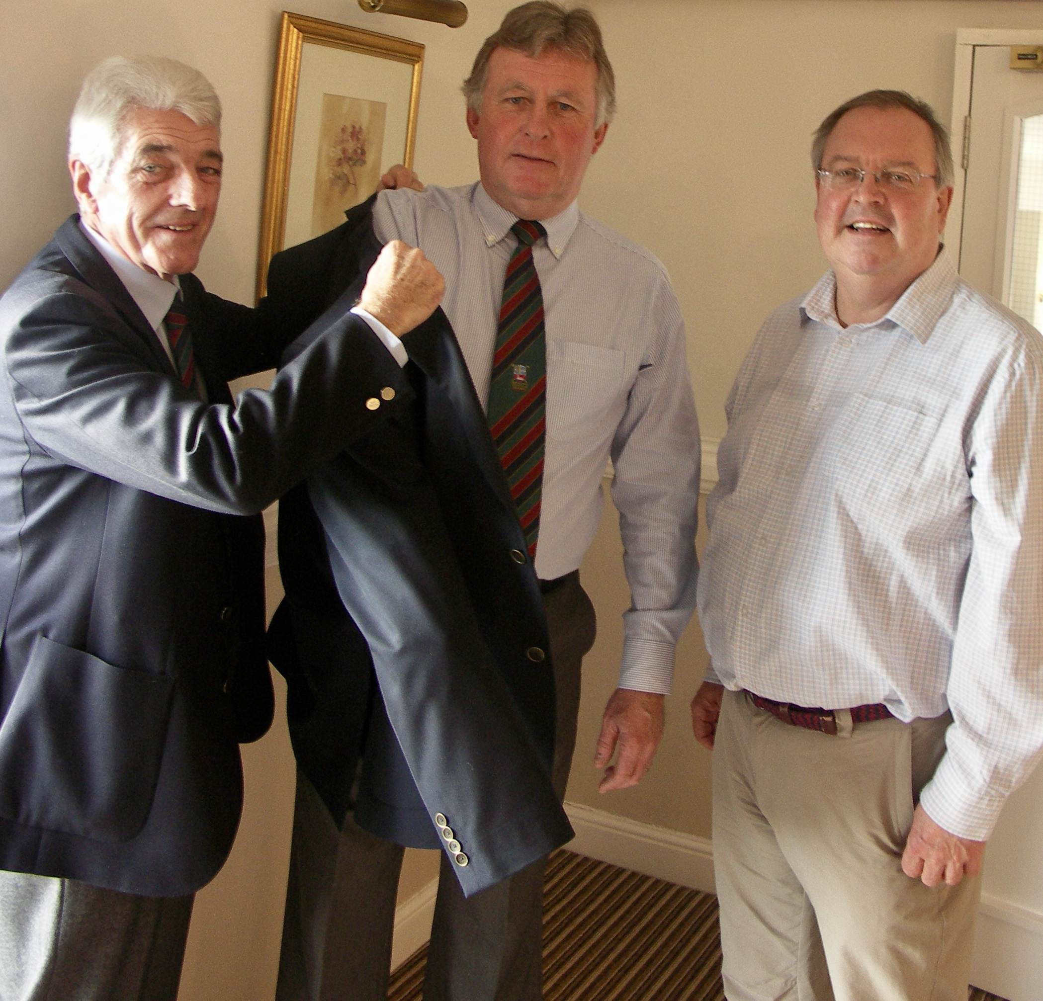 Alan Wallcroft (left) helps new Bransford seniors' captain Dave Miller don the official jacket for 2018 watched by vice-captain Andy Falconer (right)