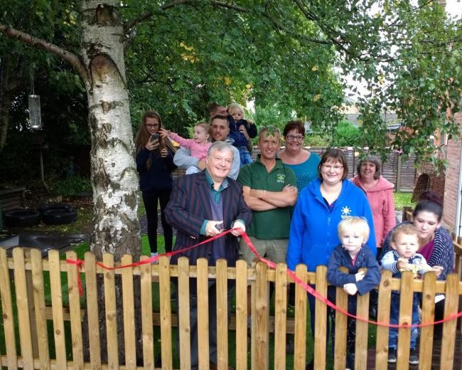 DELIGHT: A new children's garden at Mission Hall was opened by councillor Alan Amos last month. Anne Eyre is pictured in the middle at the back in a turquoise top