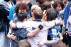 Hug: Friends of Tony Ballard, dressed in colourful clothes, embrace each other as they remember their friend. 29266129